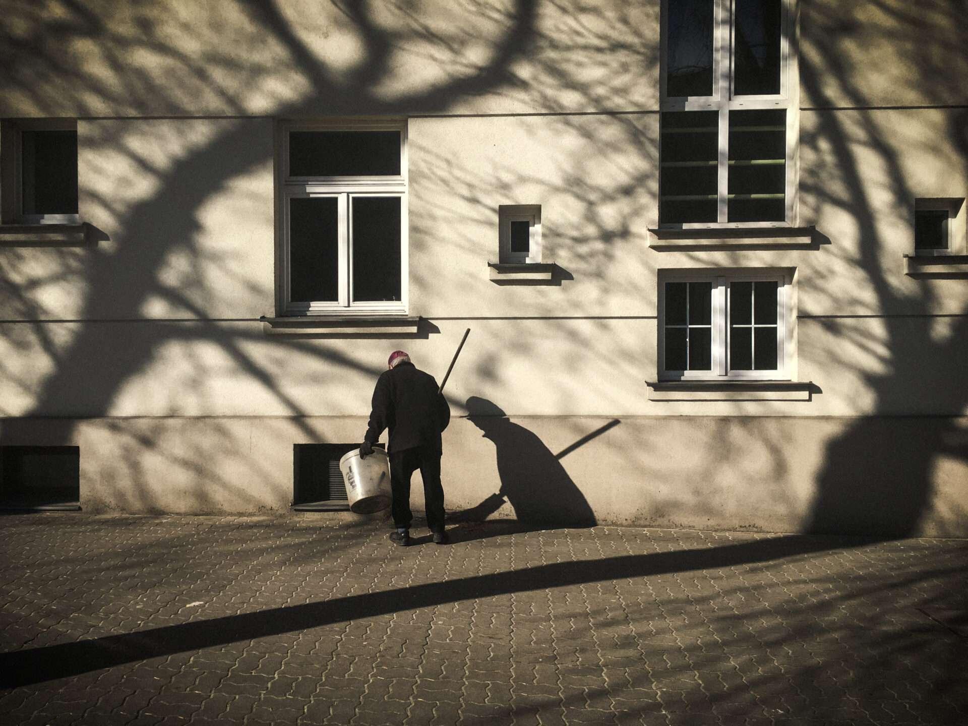 Dozorca sprząta chodnik